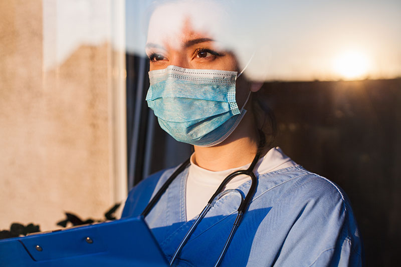 health care worker looking out window
